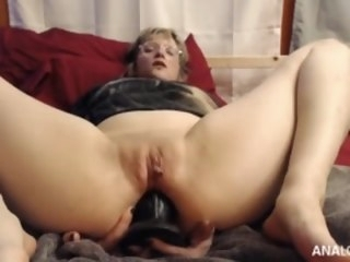 The girl in glasses masturbates anally using a large dildo pussy shaved